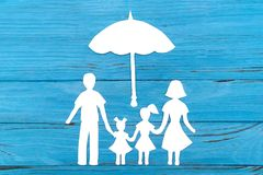 Paper silhouette of family under umbrella. On blue wooden background. Life insurance concept Stock Image