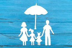 Paper silhouette of family under umbrella. On blue wooden background. Life insurance concept Royalty Free Stock Images