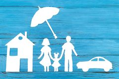 Paper silhouette of family under umbrella. With car and house, on blue wooden background. Life insurance concept Royalty Free Stock Photo