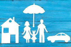 Paper silhouette of family under umbrella. With car and house, on blue wooden background. Life insurance concept Stock Photos