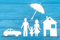 Paper silhouette of family under umbrella. With car and house, on blue wooden background. Life insurance concept Royalty Free Stock Photography