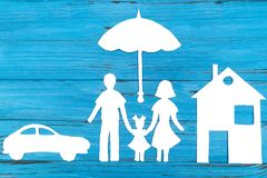 Paper silhouette of family under umbrella. With car and house, on blue wooden background. Life insurance concept Stock Images