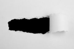 Paper slot tear. A piece of white paper is torn and the rough edges are showing on a black background stock photography