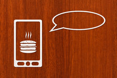 Paper smartphone with burger on screen and speech bubble Royalty Free Stock Photo