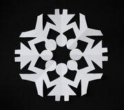 PAPER SNOWFLAKE CUT AS PEOPLE HOLDING THEIR HANDS Royalty Free Stock Photos