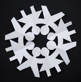 PAPER SNOWFLAKE CUT AS PEOPLE HOLDING THEIR HANDS Stock Image