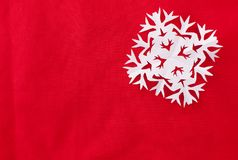 Paper snowflake on a red tablecloth. Christmas red background image with space for text insertion stock photo