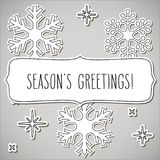 Paper snowflakes frame and Season`s greetings Stock Photography