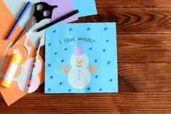 Paper snowman applique, scissors, markers, pencil, glue stick, paper sheets and scrap, snowman pattern on a wooden table Royalty Free Stock Image