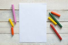 Paper and some crayons on a wooden table in a classroom. Empty copy space for Editor's text Stock Image
