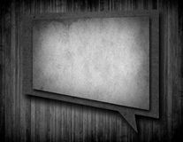 Paper speech bubble with shadow on brown wooden wall Royalty Free Stock Photography