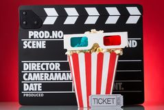 Paper square box popcorn, 3D-glasses, movie tickets and clapperb. Paper square box of popcorn, 3D-glasses, movie tickets and clapperboard on a bright red Royalty Free Stock Image