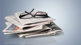 Stack of newspapers and eyeglasses on grey Royalty Free Stock Images