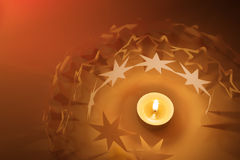 Paper stars circle around candle light. Children made star paper chains around a candle, with a red background light Stock Images