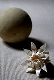 Paper and stone. Origami flower and decorative round stone Stock Image