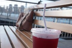 Paper straw in a take-out plastic cup, on a bench stock photos