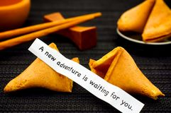 Paper strip with phrase A New Adventure is Waiting for You from. Fortune cookie, another cookie and chopsticks on black napkin background stock image