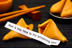Paper strip with phrase Now is the Time to Try Something New fro. M fortune cookie, another cookie and chopsticks on black napkin background Stock Images