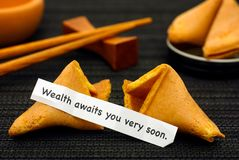 Paper strip with phrase Wealth Awaits You Very Soon from fortune. Cookie, another cookie and chopsticks on black napkin background royalty free stock photos