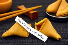 Paper strip with phrase You Will Learn a Lot Today from fortune. Cookie, another cookie and chopsticks on black napkin background stock photos