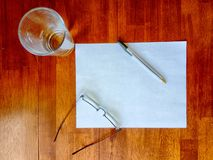 Paper on table with glass, eyeglasses, and pen Royalty Free Stock Image