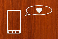 Paper tablet or smartphone and speech bubble with heart Stock Photography