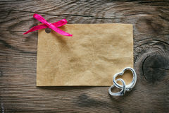 Paper tag with a pink bow, two silver heart Stock Photography