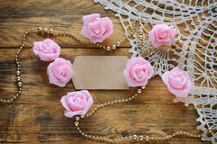 Paper tag, pink roses, golden beads, lace cloth on wooden table Royalty Free Stock Photos