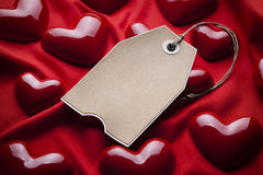 Paper tag and red hearts Royalty Free Stock Photography