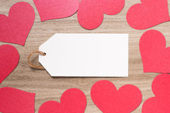 Paper tag with Red Valentines Day heart shaped paper border on wooden background Royalty Free Stock Image