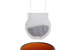 Paper teabag hanging over a cup. A white paper teabag with black tea hanging over a cup Royalty Free Stock Image