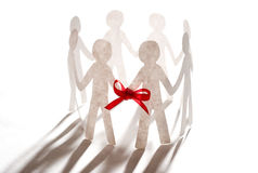 Paper team linked together with red bow Royalty Free Stock Photography