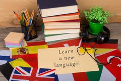 Paper with text & x22;Learn a new language!& x22;, flags, books, headphones, pencils. Learning languages concept - paper with text & x22;Learn a new language!& royalty free stock photography