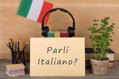 paper with text & x22;parli italiano?& x22;, flag of the Italia, books, headphones, pencils stock photo