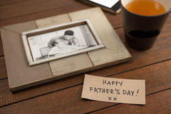 Paper with text by picture frame and coffee cup on table Stock Image