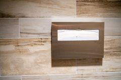 Paper toilet seat covers for hygiene in a public restroom. Dispenser is mounted to a tiled wall royalty free stock photos