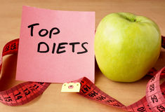 Paper with top diets, apple and measuring tape. Stock Image