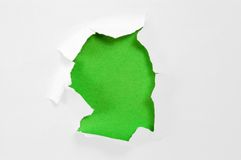 Paper with torn hole. Hole torn in paper on green background stock photo