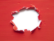 Paper torn hole. Red corrugated paper torn hole Stock Photo