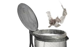 Paper tossed into trash bin on white background Stock Image