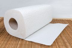 Paper towels roll with tear sheets on bamboo table mat. Roll of two-ply paper towels with tear-off sheets on the wooden bamboo table mat stock photo