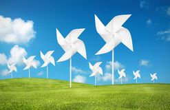 Paper toy windmill in green grass field. White paper toy windmill in green grass field Royalty Free Stock Image