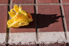 Paper Trash Left carelessly on the sidewalk. A piece of yellow trash paper in left on the brick sidewalk stock photo