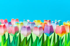 Paper tulip field with a blue background. Shallow depth of field. Focus on the front row stock image