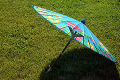 Paper Umbrella Blue. A turquoise blue umbrella with tropical flare casts its own shadow in the rich green grass. Nice as a decoration, expression and room for Stock Photography