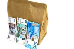 Paper universal package with products inside and three bills. In the photo there are the following objects: one bag of paper, universal, inside are products royalty free stock images