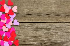 Paper Valentines Day heart side border on rustic wood Royalty Free Stock Photography
