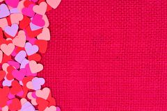 Paper Valentines Day hearts side border on pink burlap Royalty Free Stock Photo
