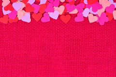 Paper Valentines Day hearts top border on pink burlap Stock Images