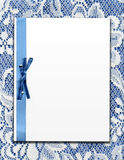Paper On Vintage Lace. Clean blank white paper board and blue ribbon and bow on real vintage white lace fabric on matching blue background. Ready for your text Stock Images